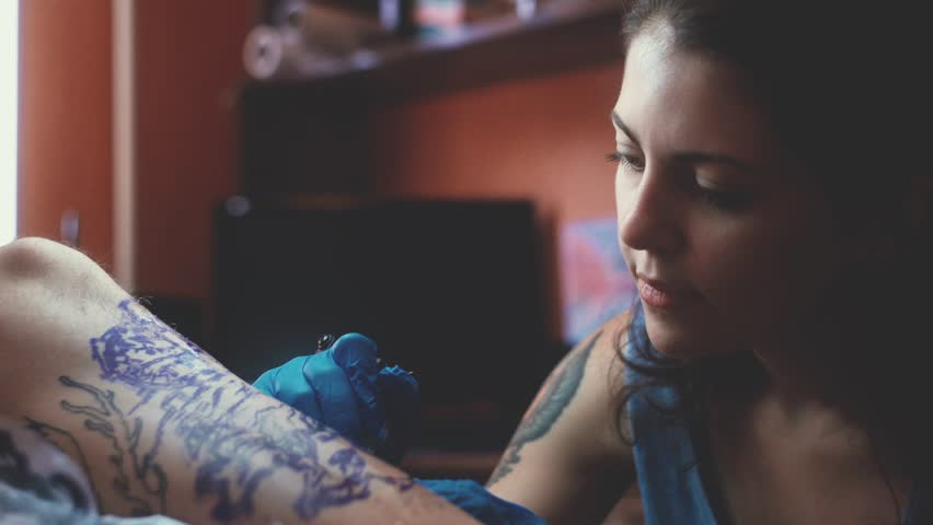Girl Tattoo Artist Tattooing His Client